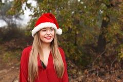 Mujer joven con el sombrero de la Navidad en el bosque Imagen de archivo libre de regalías
