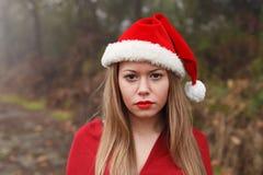 Mujer joven con el sombrero de la Navidad en el bosque Fotos de archivo libres de regalías