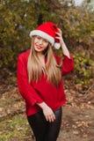 Mujer joven con el sombrero de la Navidad en el bosque Fotografía de archivo libre de regalías