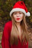 Mujer joven con el sombrero de la Navidad en el bosque Foto de archivo libre de regalías