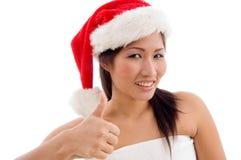 Mujer joven con el sombrero de la Navidad que muestra el pulgar para arriba Fotos de archivo