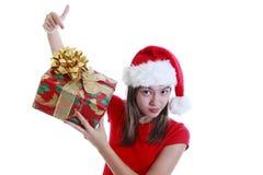 Mujer joven con el sombrero de Navidad que señala actualmente Imagenes de archivo
