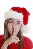 Mujer joven con el sombrero de Navidad que señala silencio Foto de archivo libre de regalías