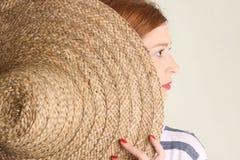 Mujer joven con el sombrero de paja grande Imágenes de archivo libres de regalías