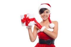 Mujer joven con el sombrero de Papá Noel que sostiene el regalo de la Navidad contra blanco Foto de archivo libre de regalías