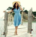 Mujer joven con el sombrero del verano que presenta en el puente Imagen de archivo libre de regalías