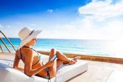Mujer joven con el sombrero que pone y que lee el eBook Foto de archivo libre de regalías