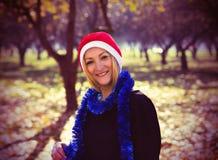 Mujer joven con el sombrero rojo de santa al aire libre Fotografía de archivo libre de regalías