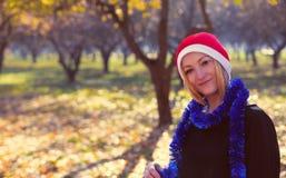Mujer joven con el sombrero rojo de santa al aire libre Imagenes de archivo