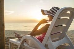 Mujer joven con el sunhat que se sienta en una silla de playa plástica imágenes de archivo libres de regalías