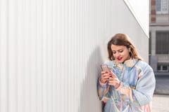 Mujer joven con el teléfono al aire libre Fotos de archivo