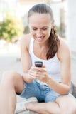 Mujer joven con el teléfono celular Fotos de archivo libres de regalías