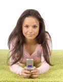 Mujer joven con el teléfono celular en la alfombra verde Foto de archivo