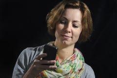 Mujer joven con el teléfono elegante Fotografía de archivo libre de regalías