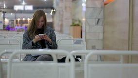 Mujer joven con el teléfono elegante en la puerta que espera en terminal Concepto del transporte aéreo con la sentada casual jove almacen de metraje de vídeo