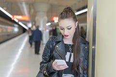 Mujer joven con el teléfono en la estación de metro Imagenes de archivo
