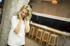 Mujer joven con el teléfono móvil Fotografía de archivo libre de regalías