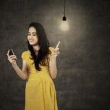 Mujer joven con el teléfono móvil debajo de la bombilla Fotografía de archivo libre de regalías