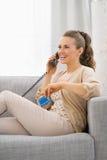 Mujer joven con el teléfono que habla de la tarjeta de crédito Foto de archivo