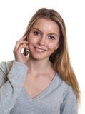 Mujer joven con el teléfono que mira la cámara Imagen de archivo libre de regalías