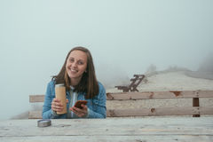 Mujer joven con el teléfono que se sienta en banco de madera y consumición caliente Foto de archivo libre de regalías