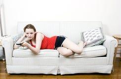 Mujer joven con el telecontrol de la TV Imágenes de archivo libres de regalías
