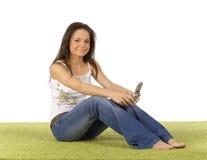Mujer joven con el teléfono celular en la alfombra verde Fotos de archivo