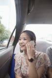 Mujer joven con el teléfono celular en taxi Imagenes de archivo