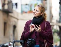 Mujer joven con el teléfono móvil al aire libre Imágenes de archivo libres de regalías