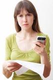 Mujer joven con el teléfono móvil y Bill Looking Worried Fotos de archivo libres de regalías