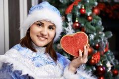 Mujer joven con el traje de la Navidad con el corazón Imagen de archivo libre de regalías