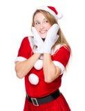 Mujer joven con el traje de la Navidad con tacto de dos manos en cara Foto de archivo libre de regalías