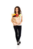 Mujer joven con el ultramarinos y las verduras Fotografía de archivo