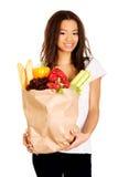 Mujer joven con el ultramarinos y las verduras Imagen de archivo