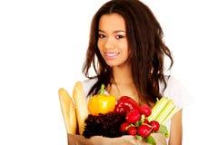 Mujer joven con el ultramarinos y las verduras Fotografía de archivo libre de regalías