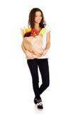 Mujer joven con el ultramarinos y las verduras Foto de archivo libre de regalías