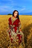 Mujer joven con el vestido ornamental que se coloca en a Fotos de archivo libres de regalías