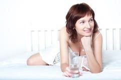 Mujer joven con el vidrio de agua dulce imagen de archivo