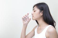 Mujer joven con el vidrio de agua dulce Fotos de archivo