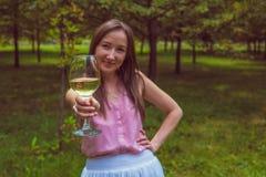Mujer joven con el vino blanco en el parque Fotografía de archivo libre de regalías