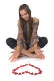 Mujer joven con en forma de corazón hecha de pétalos color de rosa imágenes de archivo libres de regalías