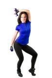 Mujer joven con entrenamiento de las pesas de gimnasia en gimnasia Foto de archivo