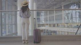 Mujer joven con equipaje en aeropuerto internacional que camina con su equipaje Pasajero de la línea aérea en un salón del aeropu almacen de metraje de vídeo