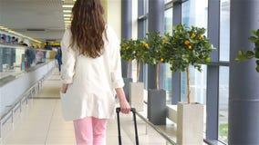 Mujer joven con equipaje en aeropuerto internacional que camina con su equipaje Pasajero de la línea aérea en un salón del aeropu almacen de video
