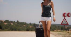 Mujer joven con equipaje en el camino almacen de video