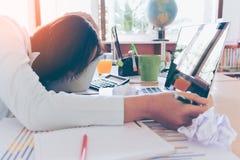 Mujer joven con exceso de trabajo y cansada que duerme en el escritorio Imagenes de archivo