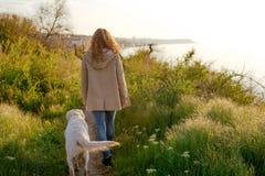 Mujer joven con golden retriever en la playa Imagenes de archivo
