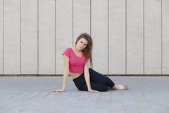 Mujer joven con la actitud seria que se sienta en el piso Fotos de archivo