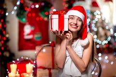 Mujer joven con la actual caja en la Navidad Imágenes de archivo libres de regalías