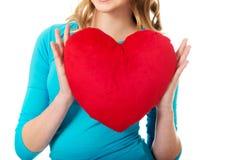 Mujer joven con la almohada en forma de corazón Imágenes de archivo libres de regalías